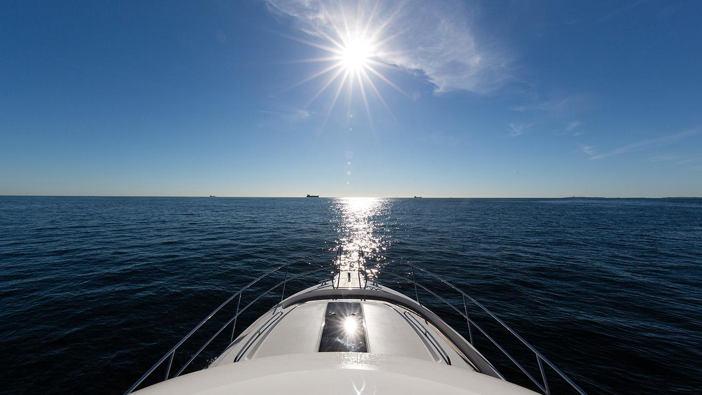Fören på Nimbus-båt pekar mot horisonten på öppet hav i vårsol