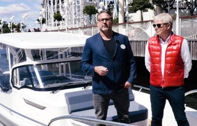 Två män står på en båt framför ett tivoli