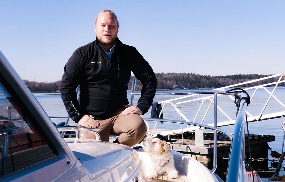 Man sitter i fören på motorbåt med hund bredvid sig
